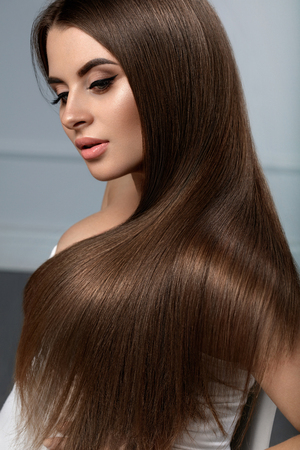 髪は長い。健全な滑らかなストレート髪の美しい女性モデル。自然な顔メイク、光沢のある光沢のある髪型、茶色の髪の色とゴージャスなブルネッ