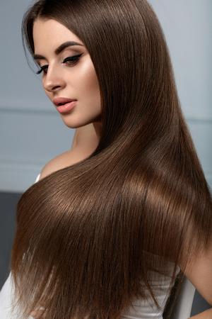 Długie włosy. Piękny model kobiety z zdrowej gładkie włosy proste. Portret przepięknych dziewczyna brunetka z naturalnym makijażu twarzy, błyszczące błyszczący fryzurę i kolor brązowy włosy. Pielęgnacja włosów. Wysoka jakość Zdjęcie Seryjne