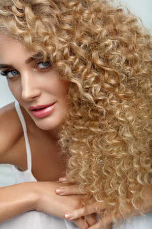 Perfect Hair. Beautiful Woman Model With Long Healthy Blonde Curly Hair. Portrait Gorgeous Sexy Girl With Natural Facial Makeup, Beauty Face And Fashion Hairstyle. Hair Care Cosmetics. High Resolution Stock Photo