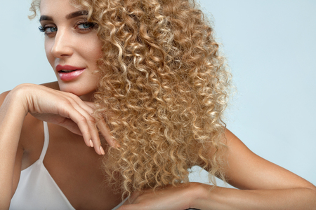 hair and beauty: Perfect Hair. Beautiful Woman Model With Long Healthy Blonde Curly Hair. Portrait Gorgeous Sexy Girl With Natural Facial Makeup, Beauty Face And Fashion Hairstyle. Hair Care Cosmetics. High Resolution Stock Photo