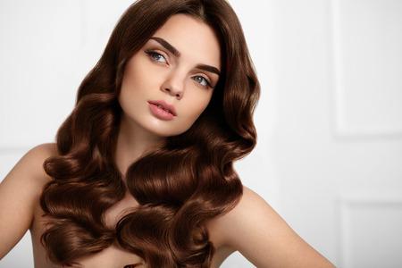 건강한 헤어. 긴 빛나는 물결 모양의 곱슬 머리 스타일을 가진 아름 다운 여자 모델입니다. 자연 메이크업의 초상화 화려한 갈색 머리 소녀, 아름다움  스톡 콘텐츠