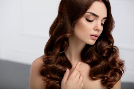 건강한 머리카락. 긴 반짝이 물결 모양의 곱슬 머리 스타일로 아름 다운 여자 모델. 자연스러운 메이크업, 아름다움 얼굴, 완벽 한 갈색 머리 색깔과 곱 스톡 콘텐츠