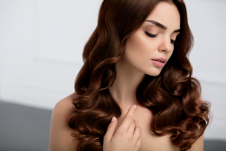 Capelli sani. Bella modello della donna con lunghi lucidi ondulati ricci Hair Style. Ritratto Splendida ragazza bruna con il trucco naturale, di bellezza del fronte, Perfect Blue Colore dei capelli e riccioli. Cosmetici. Alta qualità