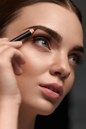 Eyebrows Shaping. Portrait Of Sexy Young Girl With Brow Pencil. Closeup Of Beautiful Glamourous Woman With Professional Makeup Contouring Brows With Eyebrow Pencil. Beauty Concept. High Resolution