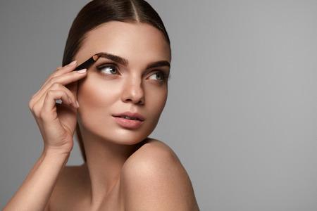 메이크업 화장품. 전문 화장품 연필을 사용 하여 아름 다운 섹시 한 여자의 근접 촬영. 아름다움 얼굴 윤곽선 눈 썹 연필로 매력적인 여성 모델의 초상 스톡 콘텐츠