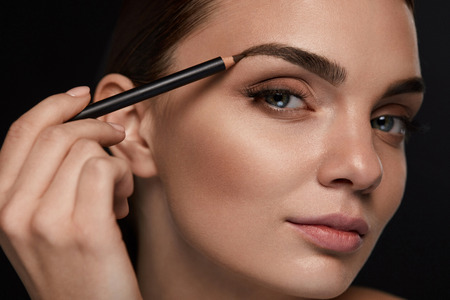 glamourous: Eyebrows Shaping. Portrait Of Sexy Young Girl With Brow Pencil. Closeup Of Beautiful Glamourous Woman With Professional Makeup Contouring Brows With Eyebrow Pencil. Beauty Concept. High Resolution
