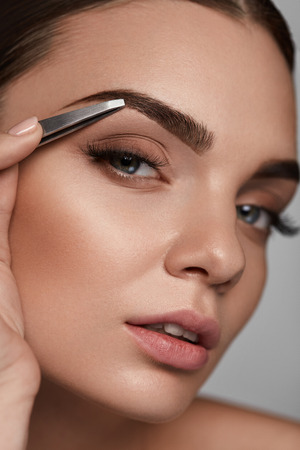 brows: Eyebrow Correction. Closeup Of Beautiful Young Woman With Perfect Makeup And Long Lashes Plucking Eyebrows. Portrait Of Sexy Female Model Face And Tweezers Near Brows. Beauty Concept. High Resolution