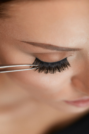 Eyelashes. Beautiful Woman Applying False Eyelashes With Tweezers. Closeup Of Young Female Model Face With Professional Facial Makeup, Smooth Skin And Long Black Thick Eye Lashes. High Resolution Stock Photo