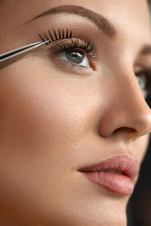 extremely: Eyelash Extension. Hand With Tweezers Applying Artificial Eyelashes On Beautiful Woman Eyes. Closeup Of Female Model Face With Long Fake Eye Lashes. Extremely Long Lashes. High Resolution Image