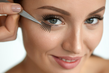 ojos hermosos: Fake Eyelashes. Hand With Tweezers Applying Artificial Eyelashes On Beautiful Woman Eyes. Closeup Of Female Model Face With Perfect Makeup, Long Black Eye Lashes. Eyelash Extension. High Resolution Foto de archivo
