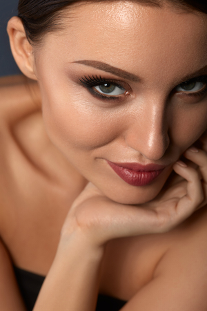 Beauty Makeup. Portrait Of Beautiful Smiling Woman With Fresh Smooth Soft Skin, Perfect Professional Facial Make-up And Long Black Fake Eyelashes. Female Model With Gorgeous Face. High Resolution