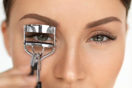Eyelash Curler. Portrait Of Beautiful Young Woman Using Beauty Tool On Curly Long Eyelashes. Closeup Of Female Model Face With Smooth Skin, Perfect Natural Makeup. High Resolution Stock Photo