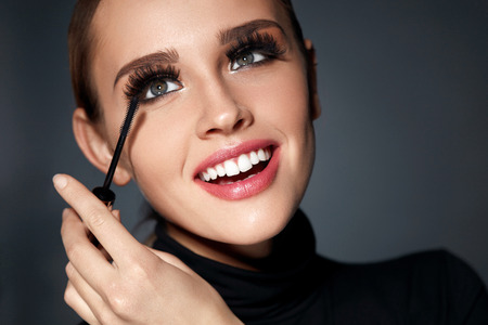 fake smile: Face Beauty. Closeup Portrait Of Beautiful Smiling Woman With Perfect Facial Makeup, Soft Smooth Skin And Long Black Eyelashes. Fashionable Girl Applying Mascara With Cosmetic Brush. High Resolution Stock Photo