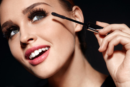 Schönheit Make-up und Kosmetik. Nahaufnahme der schönen Frau Gesicht mit weichen Haut, professionelle und perfekte Gesichts-Make-up, die schwarze Mascara auf lange dichte Wimpern mit kosmetischen Pinsel. Hohe Auflösung