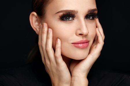Vrouwenportret van de schoonheid. Mooie modieuze vrouw met Perfect gezicht make-up, Zachte Pure schoon gezicht huid en lange zwarte dikke Valse Wimpers Op Zwarte Achtergrond. Cosmetics Concept. Hoge resolutie
