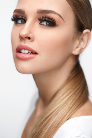 Beauty Woman Face. Closeup Of Beautiful Young Female Model With Soft Smooth Skin And Professional Facial Makeup. Portrait Of Sexy Girl With Long Fake Eyelashes And Perfect Make-up. High Resolution