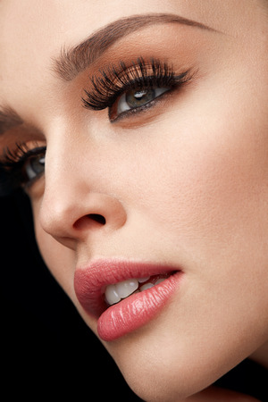 Makeup On Beauty Face. Closeup Of Beautiful Sexy Womans Face With Healthy Soft Smooth Skin And Facial Make-up. Woman With Perfect Eyebrows And Thick Long Black Eyelashes. Cosmetics. High Resolution