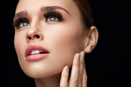 Beauty Makeup. Portrait Of Glamorous Girl With Long False Eyelashes, Perfect Professional Makeup And Smooth Skin. Closeup Of Beautiful Young Woman With Hand Near Face. Fake Eyelashes. High Resolution