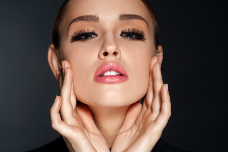 Perfect Face Makeup. Closeup Portrait Of Beautiful Sexy Woman With Professional Makeup Touching Her Smooth Soft Healthy Facial Skin. Glamorous Female Model With Long Black Eyelashes. High Resolution