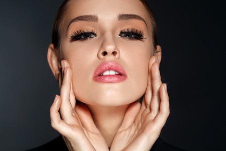 Trucco viso perfetto. Closeup ritratto di bella donna sexy con trucco professionale toccando la sua morbida Soft Skin Facial. Modello femminile affascinante con lunghe ciglia nere. Alta risoluzione Archivio Fotografico - 71353286