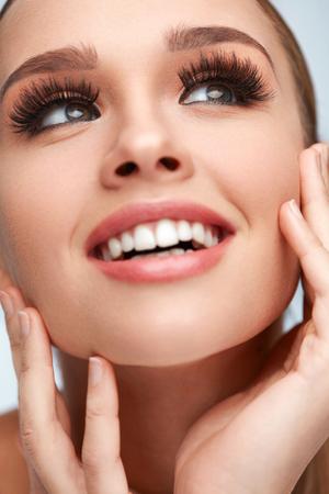 Schoonheid vrouw gezicht. Close-up van Betoverend Meisje met Handen wat betreft Zachte Vlotte Huid. Portret van mooie Sexy vrouw met perfecte gezichts make-up en lange zwarte nep wimpers. Cosmetics. Hoge resolutie