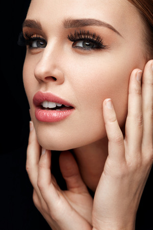 woman portrait: Perfect Face Makeup. Closeup Portrait Of Beautiful Sexy Woman With Professional Makeup Touching Her Smooth Soft Healthy Facial Skin. Glamorous Female Model With Long Black Eyelashes. High Resolution