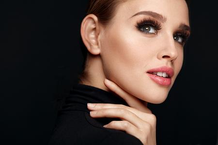 Schoonheid vrouw gezicht. Portret van mooie Sexy jonge vrouw met perfecte gezichts make-up, zachte frisse gezonde huid en dikke lange zwarte wimpers. Glamoureuze meisje op zwarte achtergrond. Hoge resolutie