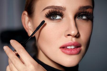 マスカラー。美容化粧, 新鮮な柔らかい肌黒い長い太いまつげ化粧ブラシでマスカラーを適用すると美しい若い女性の顔のクローズ アップ。メイク 写真素材