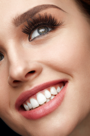 fake smile: Beauty Makeup. Closeup Of Beautiful Smiling Woman Face With Long Thick Fake Eyelashes And Perfect Facial Makeup. Happy Sexy Female With Soft Skin, White Teeth And Perfect Smile. High Resolution