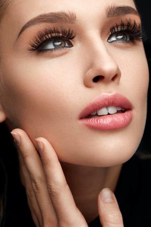 Belleza de la cara. Mujer Sexy Con fresco sano de tonos suaves con la piel perfecta y el maquillaje facial. Primer De La Hembra Joven Modelo Con larga Negro gruesas pestañas falsas, falsos latigazos del ojo. Alta resolución