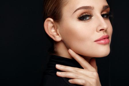 Schönheit Make-up. Nahaufnahme der schönen lächelnden Frau Berühren weich glatte Gesichtshaut. Portrait von sexy junge weibliche Modell mit Professional Make-up und lange schwarze Wimpern. Kosmetika. Hohe Auflösung