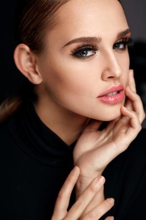 Vrouwenportret van de schoonheid. Mooie modieuze vrouw met Perfect gezicht make-up, Zachte Pure schoon gezicht huid en lange zwarte dikke Valse Wimpers Op Zwarte Achtergrond. Cosmetics Concept. Hoge resolutie Stockfoto