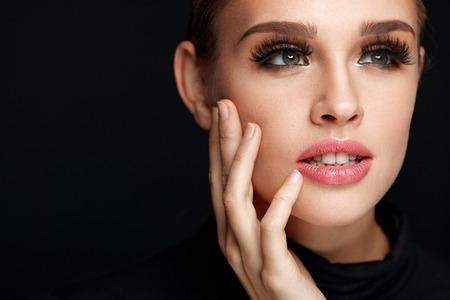 아름다움 여자 얼굴입니다. 완벽한베이스 메이크업, 소프트 신선한 건강 피부와 두꺼운 긴 검은 속눈썹 아름 다운 섹시 한 젊은 여자의 초상화입니다.