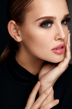 Beauty Woman Portrait. Beautiful Fashionable Woman With Perfect Facial Makeup, Soft Pure Clean Face Skin And Long Black Thick Fake Eyelashes On Black Background. Cosmetics Concept. High Resolution Stok Fotoğraf