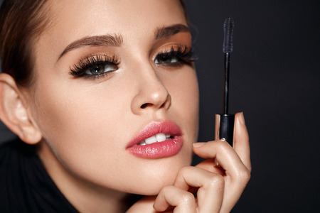 Facial Beauty. Closeup Of Sexy Woman With Beautiful Face And Mascara Brush In Hand. Portrait Of Glamorous Girl With Perfect Makeup, Smooth Skin And Long Black Fake Eyelashes On Eyes. High Resolution