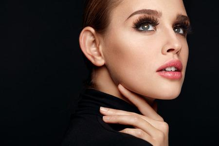 Beauty Frau Gesicht. Portrait der schönen sexy junge Frau mit einer perfekt Gesichtsschminke, weiche Frische gesunde Haut und starke lange schwarze Wimpern. Bezauberndes Mädchen auf schwarzem Hintergrund. Hohe Auflösung