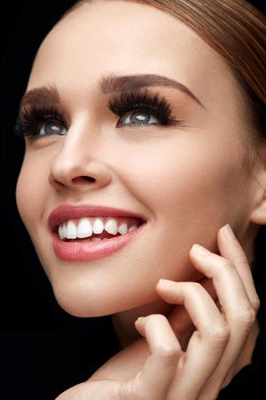 Lange zwarte wimpers. Portret van mooie Sexy jonge vrouw met gladde zachte huid en perfecte make-up. Lachende vrouw met valse wimpers op ogen aan haar gezicht te raken. Schoonheid Cosmetica. Hoge resolutie Stockfoto