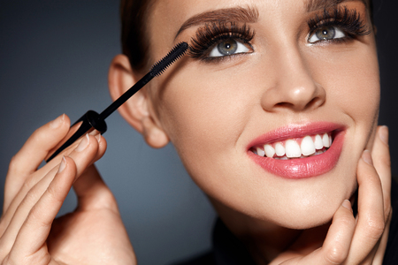 smiling face: Face Beauty. Closeup Portrait Of Beautiful Smiling Woman With Perfect Facial Makeup, Soft Smooth Skin And Long Black Eyelashes. Fashionable Girl Applying Mascara With Cosmetic Brush. High Resolution Stock Photo