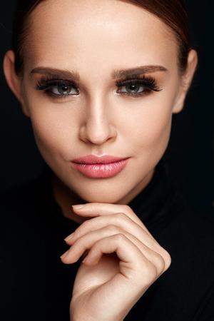 뷰티 메이크업입니다. 아름 다운 웃는 여자를 터치 소프트 부드러운 얼굴 피부의 근접 촬영입니다. 전문 메이크업과 긴 검은 속눈썹 섹시한 젊은 여성
