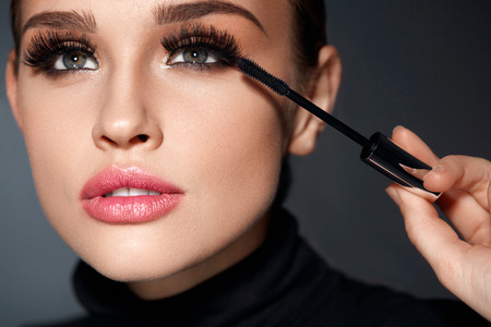 Beauty Make-up. Portrait Of Beautiful Young Woman With Fake Eyelashes Applying Black Mascara On Lashes, Holding Brush In Hand. Sexy Female With Soft Skin And Perfect Makeup. Cosmetics. High Resolution