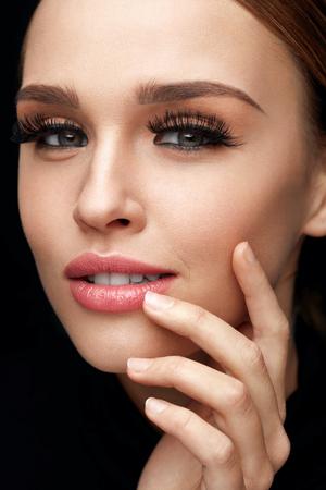 顔メイク。黒い長い太い偽まつげとプロのメイクアップ彼女の新鮮な柔らかい滑らかな顔の皮膚に触れる美しいセクシーな若い女性のポートレート