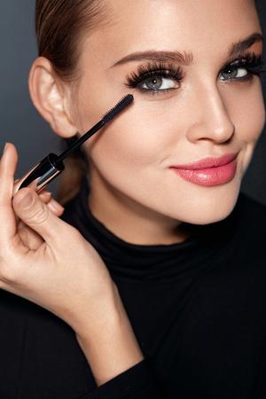 아름다움 메이크업 및 화장품입니다. 부드러운 피부, 완벽 한 전문 얼굴 메이크업으로 아름 다운 여자 얼굴의 근접 촬영 코스메틱 브러시와 긴 두꺼운