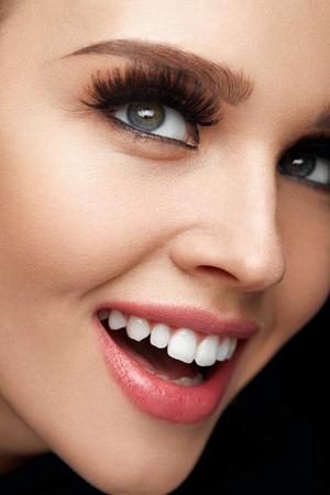 美容化粧。太くて長い偽のまつげと完璧な顔メイク美しい笑みを浮かべて女性顔のクローズ アップ。柔らかい肌、白い歯と完璧な笑顔を持つ幸せな 写真素材