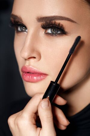 Makeup Cosmetics. Beautiful Sexy Girl With Glamorous Makeup, Smooth Healthy Skin And Long Black Eyelashes. Closeup Of Young Female Face And Mascara Brush In Hand. Beauty Concept. High Resolution