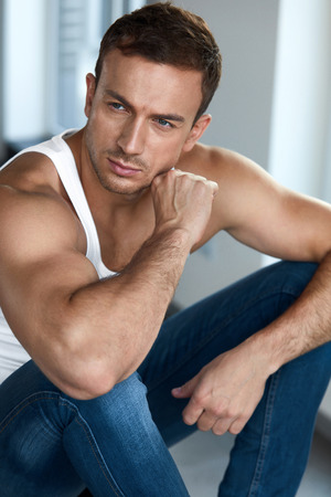 Handsome Young Man With Beautiful Face, Soft Skin And Stubble Beard. Portrait Attractive Healthy Sexy Male Model In White Vest, A-shirt Sitting Indoors. Men Beauty And Mans Health. High Resolution