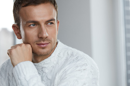 Handsome Young Man With Beautiful Face, Smooth Soft Facial Skin And Stubble Beard. Portrait Attractive Male Model In White Sweater Indoors. Beauty, Skin Care And Man's Health Concepts. High Resolution