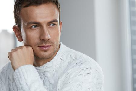 Przystojny młody człowiek z piękną twarz, soft twarzy Skóry I zarost. Portret Atrakcyjne Male Model w biały sweter w pomieszczeniach. Urody, pielęgnacji skóry i męskie zdrowie Concepts. Wysoka rozdzielczość Zdjęcie Seryjne