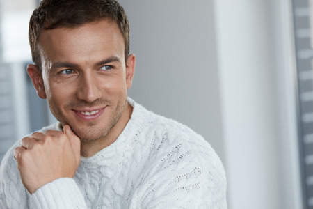 Handsome Young Man With Beautiful Face, Smooth Soft Facial Skin And Stubble Beard. Portrait Attractive Male Model In White Sweater Indoors. Beauty, Skin Care And Mans Health Concepts. High Resolution