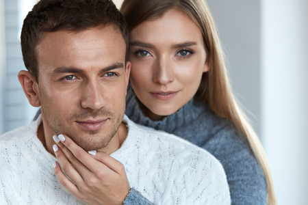 Skin Care. Beautiful Couple In Love Indoors Close Up. Loving Young Woman With Fresh Facial Makeup Touching Handsome Man Soft Face Skin, Embracing From Behind. Romantic Relationships. High Resolution