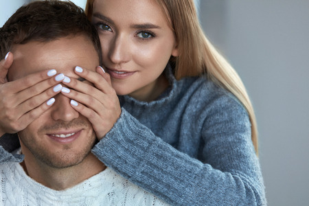 Happy Young Couple In Love. Beautiful Smiling Loving Woman With Fresh Face Makeup, Smooth Soft Skin In Warm Clothes Having Fun Closing Handsome Man Eyes With Hands. Skin Care Concept. High Resolution